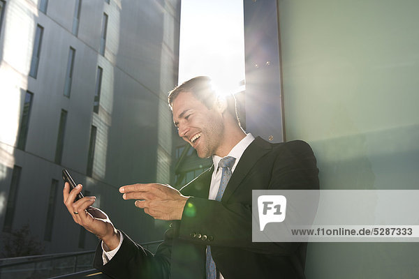 Fröhlicher Geschäftsmann schaut auf Handy im Freien