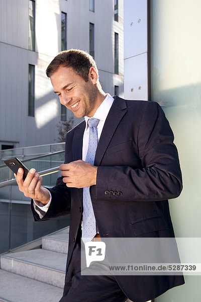Lächelnder Geschäftsmann schaut auf Handy im Freien