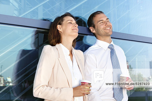 Geschäftsmann und Geschäftsfrau mit Coffee to Go im Freien