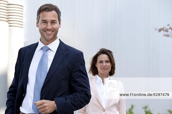 Lächelnder Geschäftsmann und Geschäftsfrau im Freien