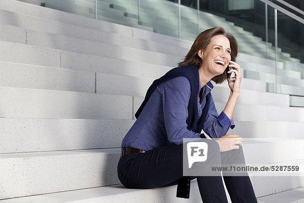 Lachende Geschäftsfrau telefoniert mit Handy auf einer Treppe