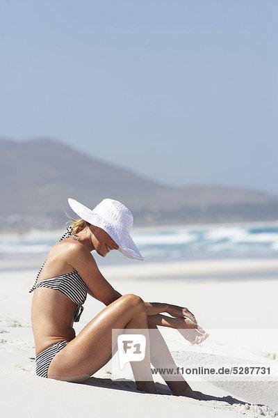 Mädchen am Strand sitzen