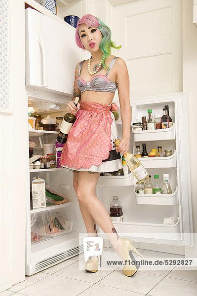 Frau  stehend an Kühlschrank mit Weinflasche