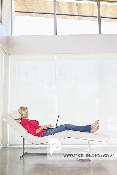 Full length of woman lying on deck chair with laptop