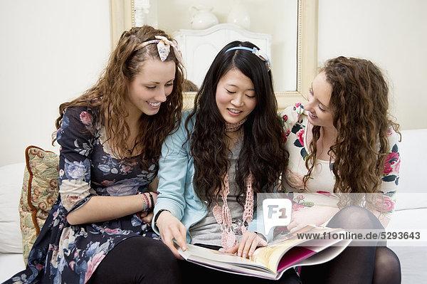 Junge Frauen betrachten Zeitschriften auf einem sofa