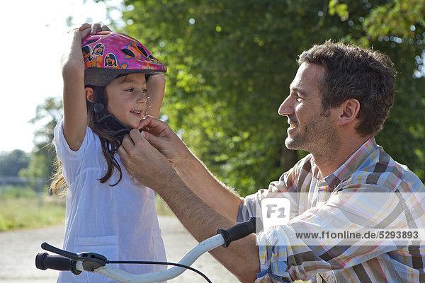 Vater schließt den Helm seiner Tochter auf dem Fahrrad