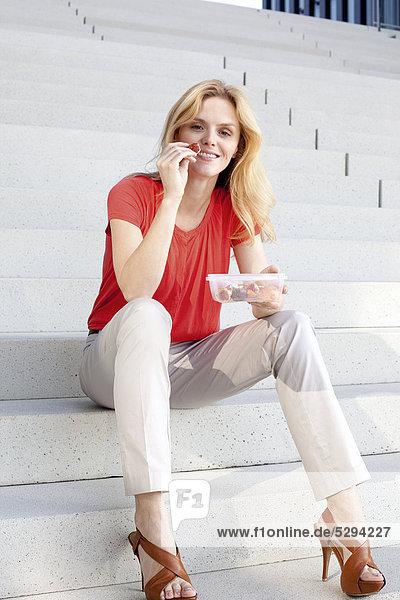Blonde Frau isst einen Snack auf einer Treppe