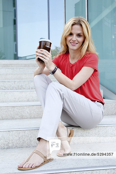 Blonde Frau mit Coffee to Go auf einer Treppe
