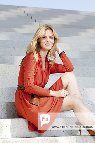 Frau in rotem Kleid sitzt auf einer Treppe