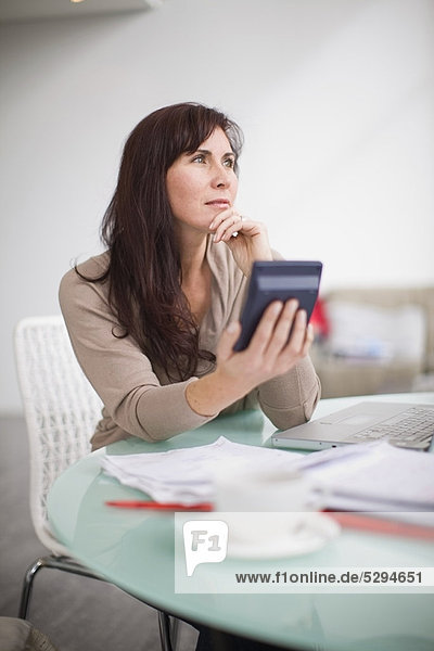Woman paying her bills at home