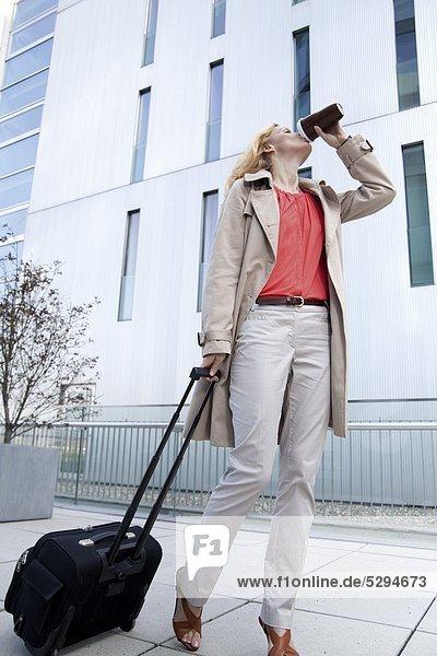 Geschäftsfrau mit Trolley auf dem Bürgersteig trinkt Kaffee