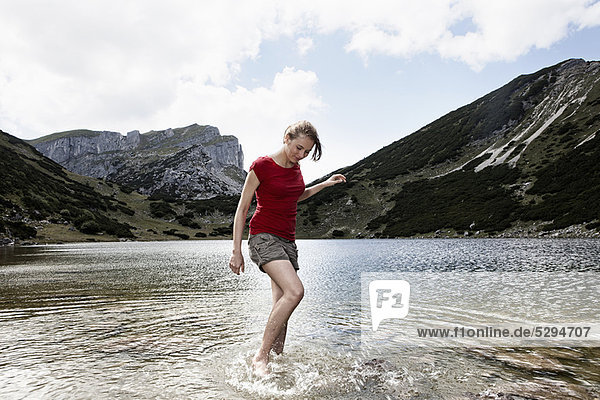 Woman standing in still lake