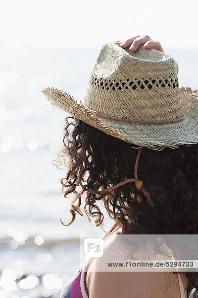 Frau mit Sonnenhut am Strand