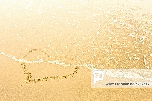 Herz im Sand von Wellen weggespült