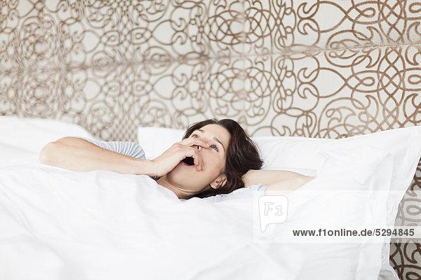 Gähnende Frau im Bett