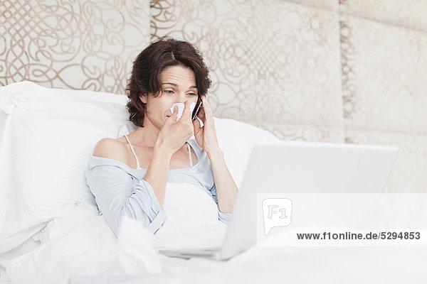 Frau  die ihre Nase im Bett schnäuzt.