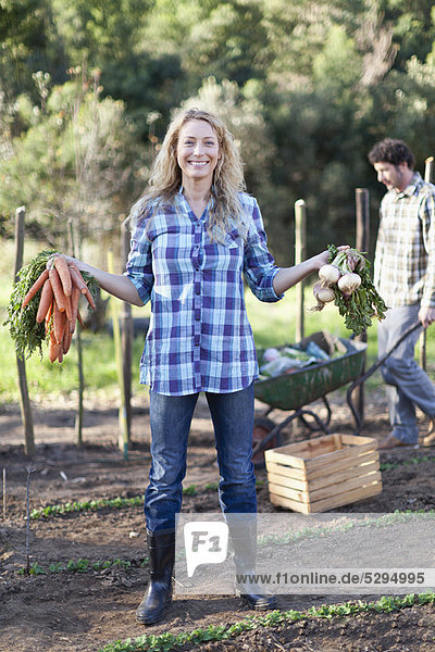 Frau  Gemüse  Garten  aufheben