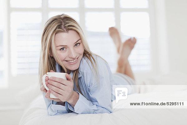 Frau trinkt eine Tasse Kaffee auf dem Bett