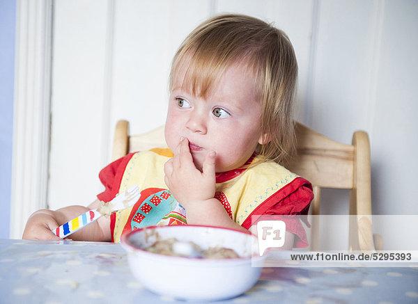 Kleinkind Mädchen im Lätzchen beim Essen am Tisch