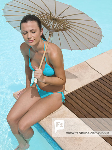 sitzend Frau Regenschirm Schirm unterhalb