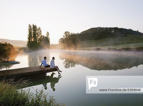 Couple relaxing on dock of lake