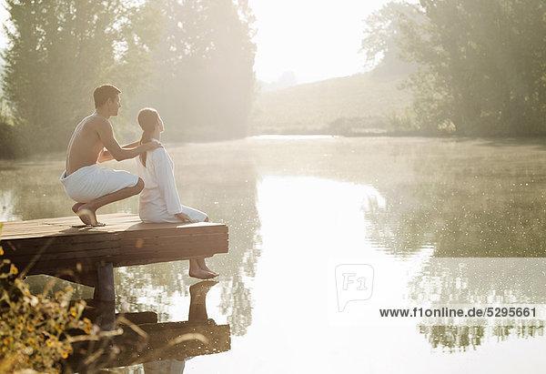 Ein Paar entspannt auf dem Dock des Sees