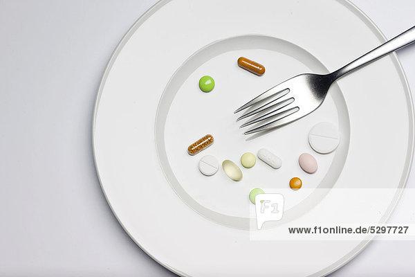 Medikamente auf Teller mit Gabel