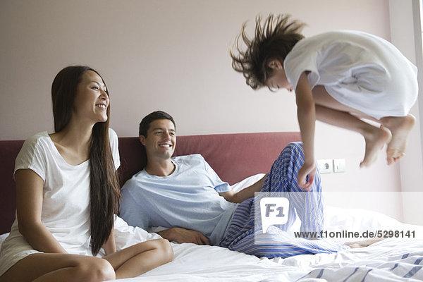 Eltern sehen zu  wie der junge Sohn auf das Bett springt.