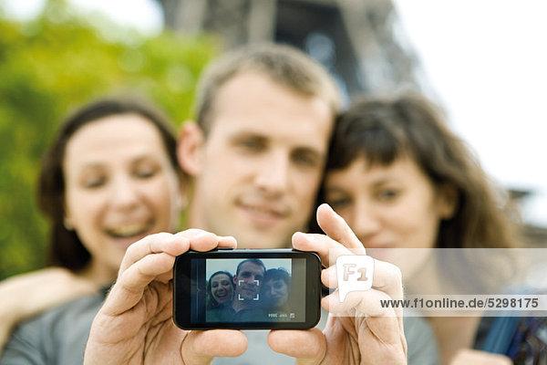 Mann fotografiert sich mit zwei Freundinnen per Handy