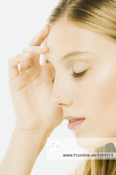 Woman with eyes closed  touching forehead  side view