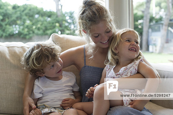 Mother and two young children cuddling on sofa