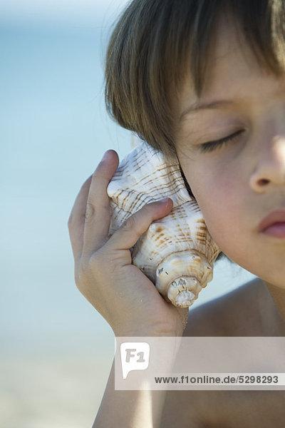 Junge hört Muschelschale mit geschlossenen Augen