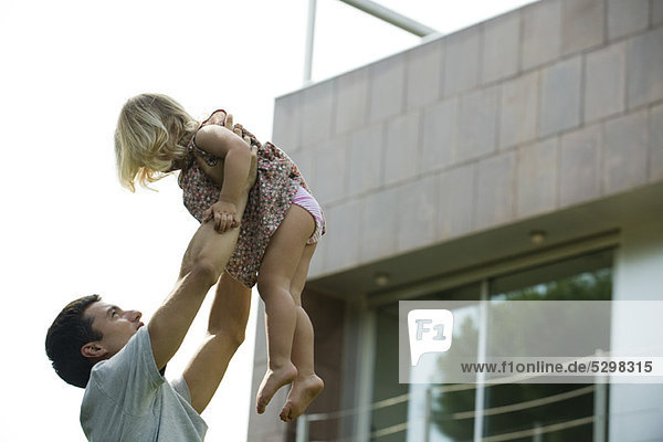 Father lifting young daughter in the air