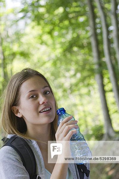 Frau hält abgefülltes Wasser im Wald.
