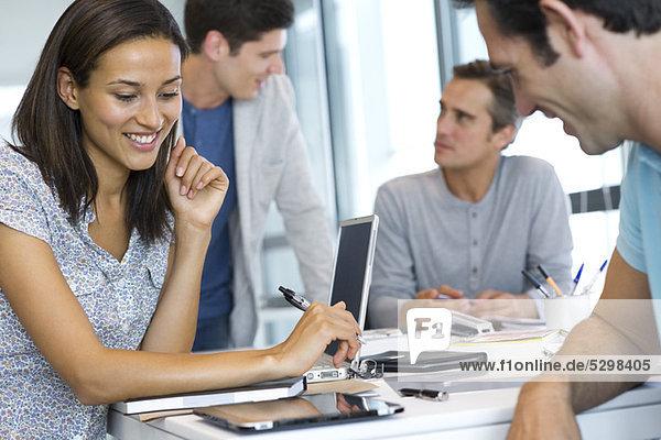 Kollegen  die mit dem digitalen Tablett im Büro arbeiten