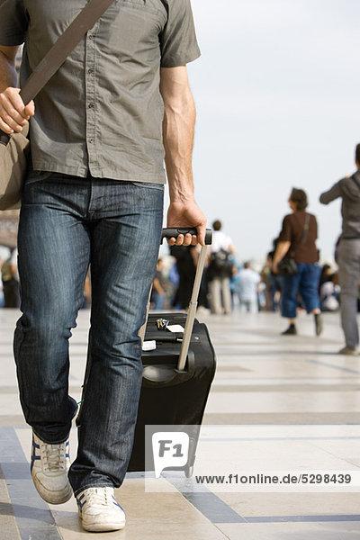 Männlicher Reisender mit Gepäck  beschnitten