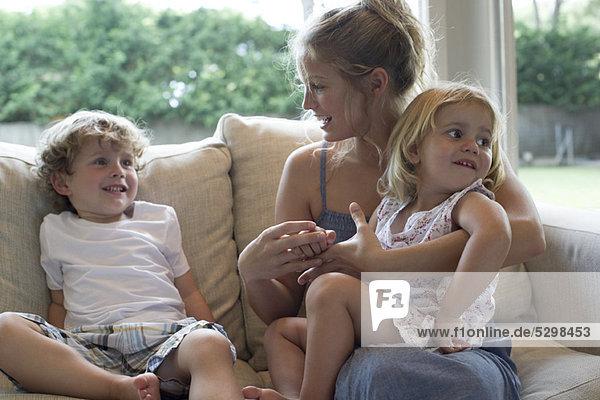 Mutter und zwei kleine Kinder sitzen zusammen auf dem Sofa.
