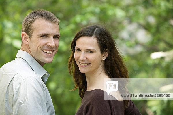 Paar lächelt über die Schultern vor der Kamera