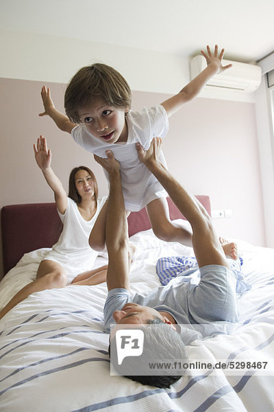 Family together on bed  father lifting son in the air