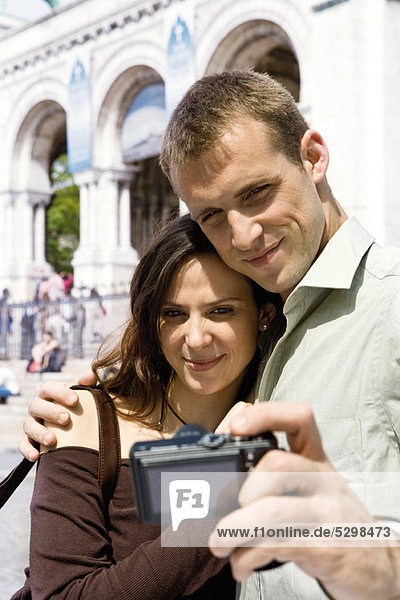 Man photographing himself and his girlfriend with digital camera