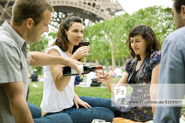 Friends enjoying wine at picnic near Eiffel Tower  Paris  France