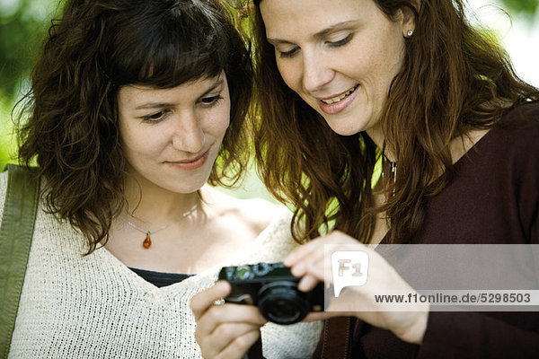 Woman showing digital camera to friend