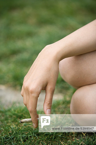 Woman holding a marijuana joint  cropped