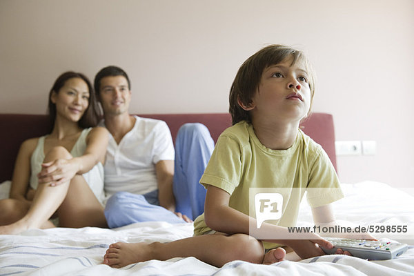 Boy watching TV in bed with his parents