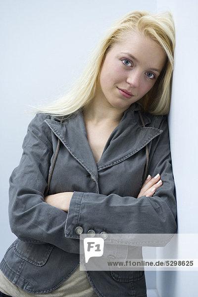 Junge Frau an der Wand lehnend mit gefalteten Armen  Portrait