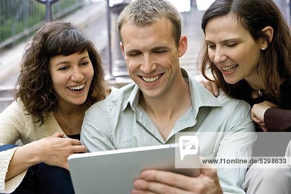 Freunde  die ein digitales Tablett im Freien benutzen