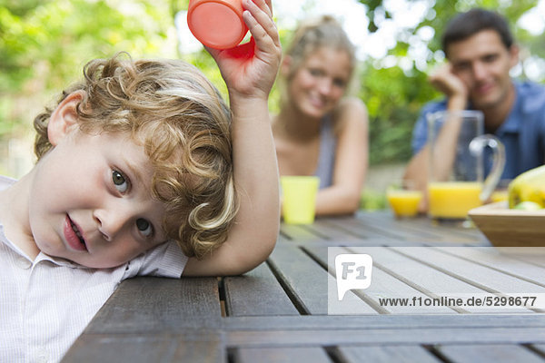Little boy relaxing at picnic table with parents