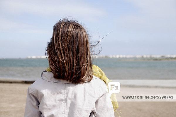 Mädchen mit Blick auf den Ozean  Rückansicht