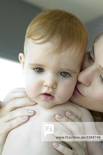 Mutter küsst Babys Wange