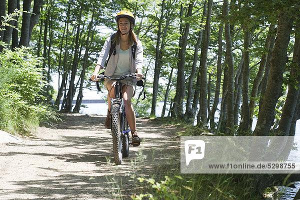 Frau fährt Fahrrad im Wald